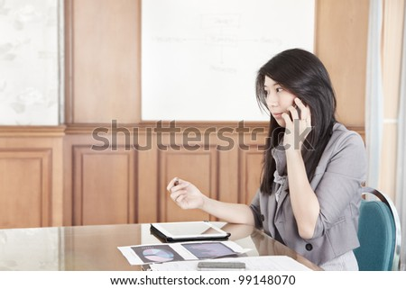 Chinese businesswoman is talking on the phone - stock photo
