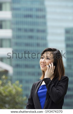 Chinese businesswoman using a Cell Phone, outside in modern city. Asian or Chinese woman talking on smartphone.  - stock photo