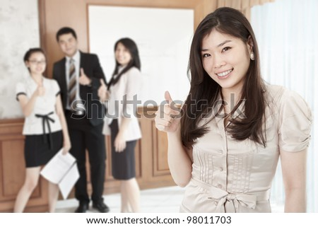 Chinese businesswoman with her thumb up smiling to camera in the office