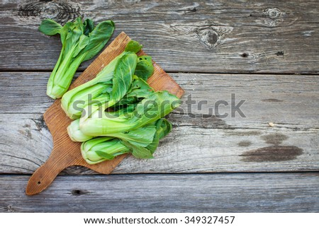 Chinese cabbage, Bok Choy, on rustic wooden background. Above view.