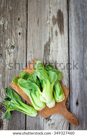 Chinese cabbage, Bok Choy, on rustic wooden background. Above view. - stock photo