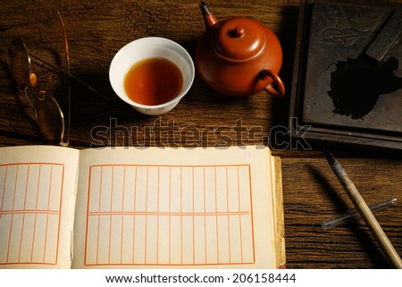 Chinese calligraphy and ink stone set on table with tea bowl, teapot, eyeglasses. Warm tone color. - stock photo