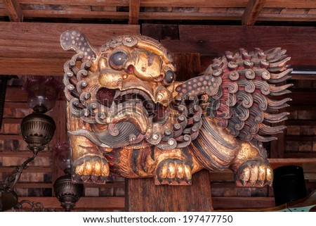 Chinese carving wooden lion decorated by stick to pillar