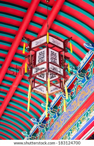 Chinese ceiling lamp on red ceiling in the temple