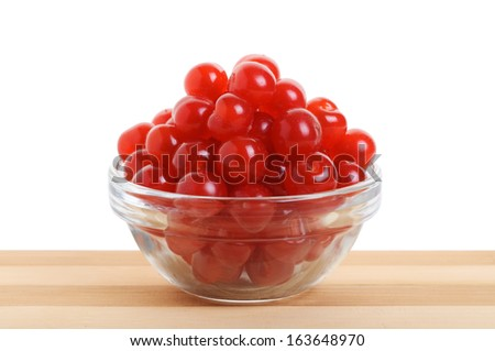Chinese cherry in a clear glass bowl on a table made of bamboo. White background. - stock photo
