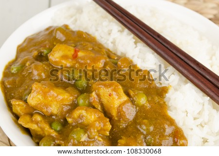 Chinese Chicken Curry with green peas and onions served with steamed rice. Close up. - stock photo