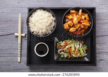 Chinese chicken sweet and sour sauce, served with rice and vegetables on woodboard - stock photo