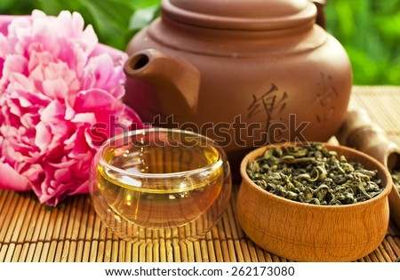Chinese clay teapot with glass cup, green tea and peony flower - stock photo
