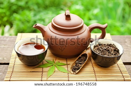 Chinese clay teapot with green and puer tea  - stock photo
