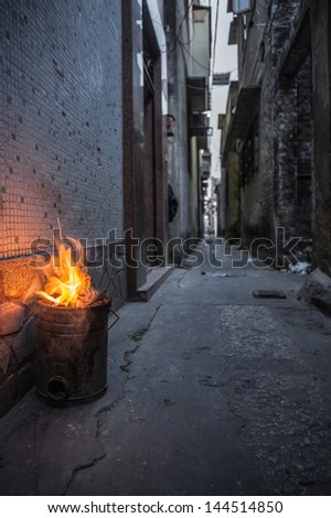 Chinese coal stove burning in a back alley in Shunde District of Foshan City, Guangdong Province in Southern China.  - stock photo