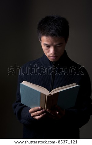 Chinese college student reading a book in sweater - stock photo