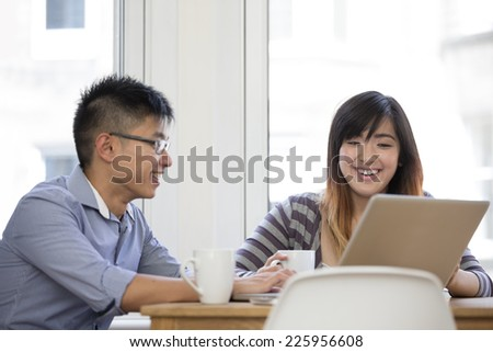 Chinese couple at home using a laptop. Couple sitting at a table.