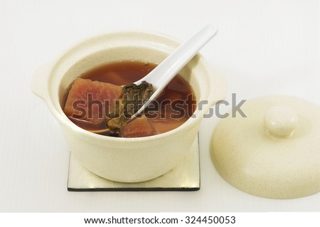Chinese cuisine of double boil soup of red beetroots and oysters.  This nutritional hot soup is served in a soup bowl on coaster and have cover to keep warm.  White background.