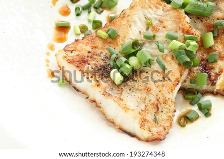 Chinese cuisine, pan fried Pacific cod with scallion and soy sauce on top - stock photo