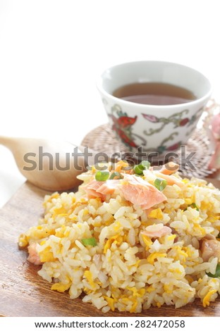 Chinese cuisine, salted Salmon fish and egg fried rice with black tea on background - stock photo