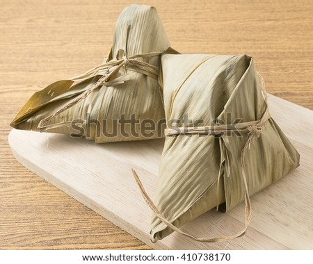 Chinese Cuisine, Two Zongzi or Sticky Rice Dumpling Served on Wooden Board for Dragon Boat Festival. - stock photo