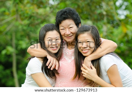 chinese daughter and mother on green outdoor