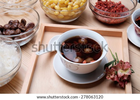 Chinese Dessert,lotus root and ginkgo nut in longan syrup on wood - stock photo