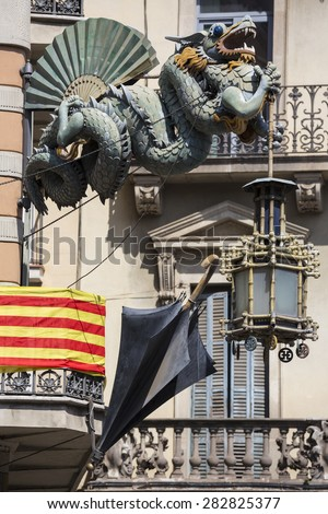 Chinese Dragon and umbrella, modernism architecture (Casa Bruno Cuadros),with the Catalan flag background, in Barcelona, Spain. Is an old store of umbrellas, canes and fans of mid-nineteenth century.