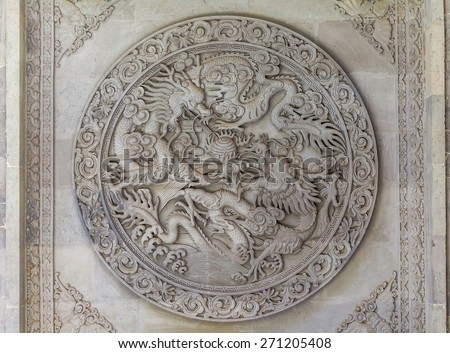 Chinese dragons engraving embossed in stone on the Buddha Temple walls, Gansu province, China. - stock photo