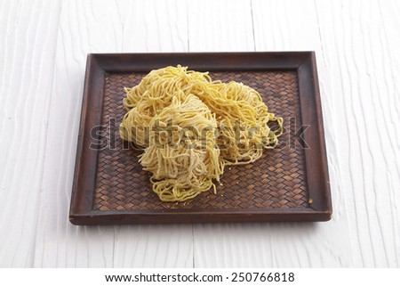 chinese dry noodle in wooden dish on white background
