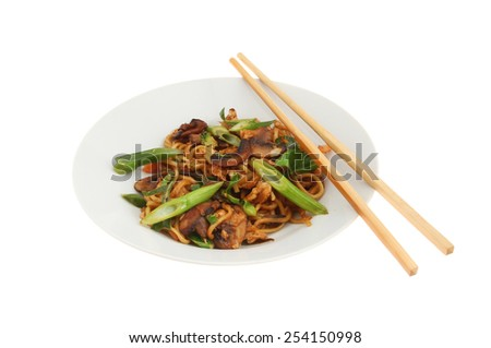 Chinese egg noodle stir fry in a bowl with chopsticks isolated against white - stock photo