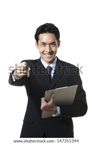 Chinese estate agent holding house keys. Isolated on a white background.