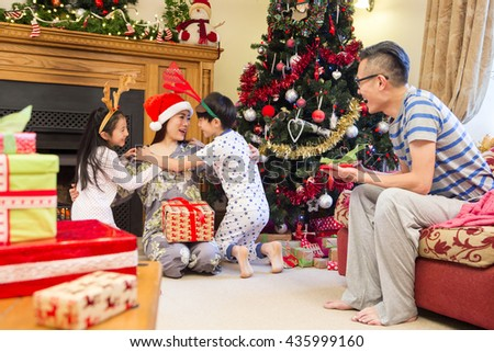 Chinese family enjoying Christmas in their home. The children are cuddling their Mother who is sitting by the Christmas tree with presents.  - stock photo