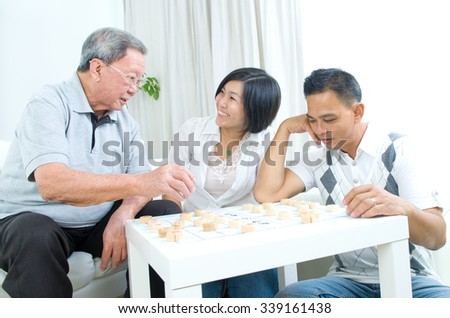 Chinese family playing Chinese chess at home, senior father with his  adult son and daughter. - stock photo