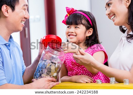 Chinese family saving money for college fund of child, putting coins in jar - stock photo