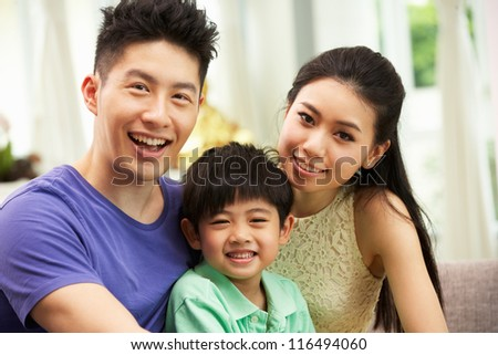Chinese Family Sitting And Relaxing On Sofa Together At Home