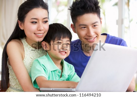 Chinese Family Sitting At Desk Using Laptop At Home - stock photo
