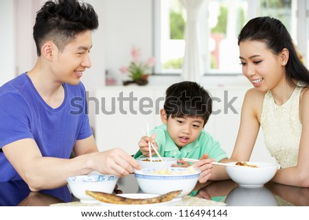 Chinese Family Sitting At Home Eating A Meal - stock photo