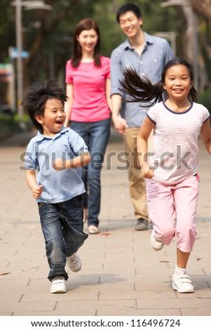Chinese Family Walking Through Park With Running Children - stock photo