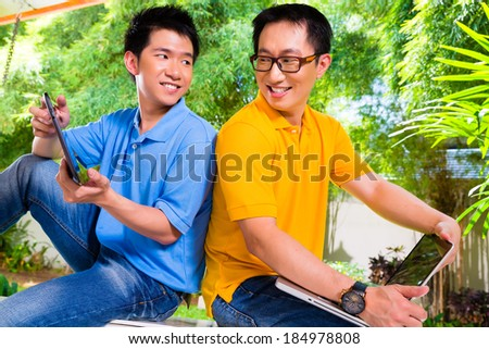 Chinese father talking with his son, they enjoying the leisure time together with a tablet computer and laptop - stock photo