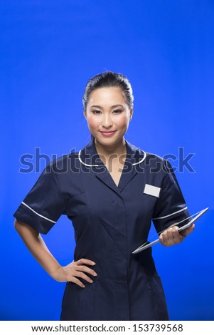 Chinese Female nurse holding a digital tablet & wearing a green scrubs plus stethoscope. Asian female model on blue background.
