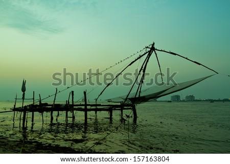 Chinese fishing net at sunset in Cochin, Fort Kochi, Kerala, India - stock photo