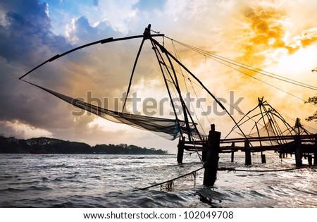 Chinese Fishing nets at dramatic sunset sky background on Vypeen Island in Kochi, Kerala, India - stock photo