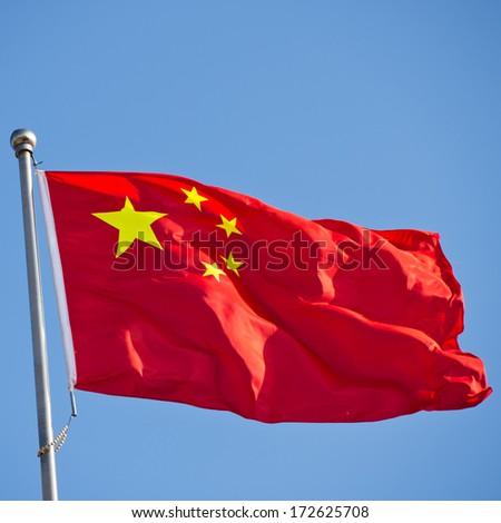 Chinese flag with flag pole waving in the wind over blue sky background. - stock photo