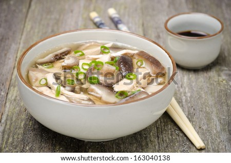 Chinese food - bowl of soup with chicken, shiitake mushrooms and green onions, soy sauce, close-up - stock photo