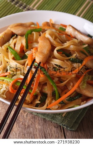 Chinese Food: Chow mein with chicken and vegetables on a table close-up. vertical  - stock photo