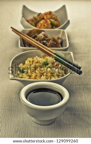 Chinese food composition with cantonese rice, noodles with prawns and beef with mushrooms - stock photo