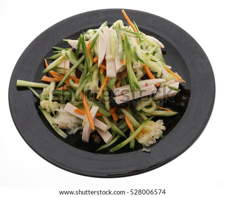 Chinese food. Cucumber salad with ham, black and whie mushrooms in black plate isolated on white. Closeup.