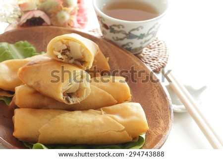 Chinese food, half section spring roll on lettuce with tea on background - stock photo