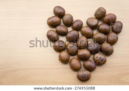Chinese food, Roasted chestnuts arrange into a heart shape on wooden background. - stock photo