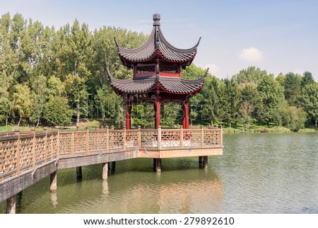Chinese gazebo with a gallery on the lake - stock photo