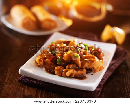 chinese general tso's chicken with fortune cookie and egg rolls - stock photo