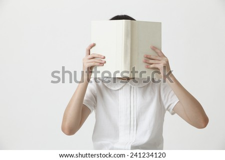 chinese girl holding a blank cover book covering her face - stock photo