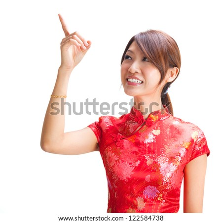 Chinese girl in traditional Chinese cheongsam pointing at blank space, isolated on white background - stock photo