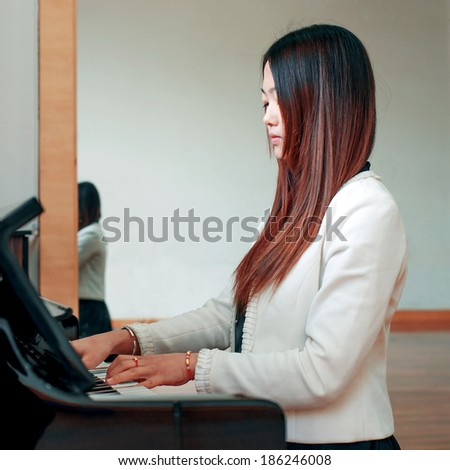 Chinese girl playing the piano - stock photo